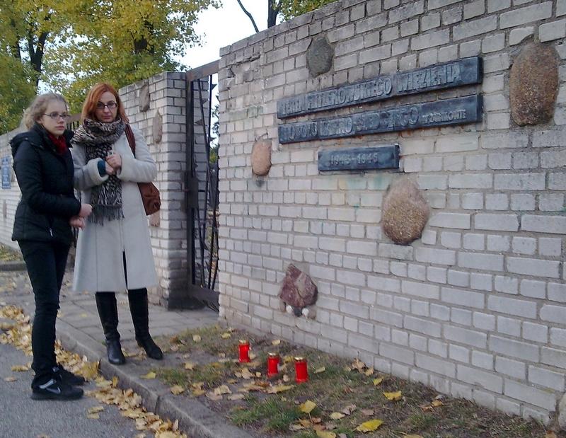 Znicze pod murem Muzeum Martyrologii w Żabikowie