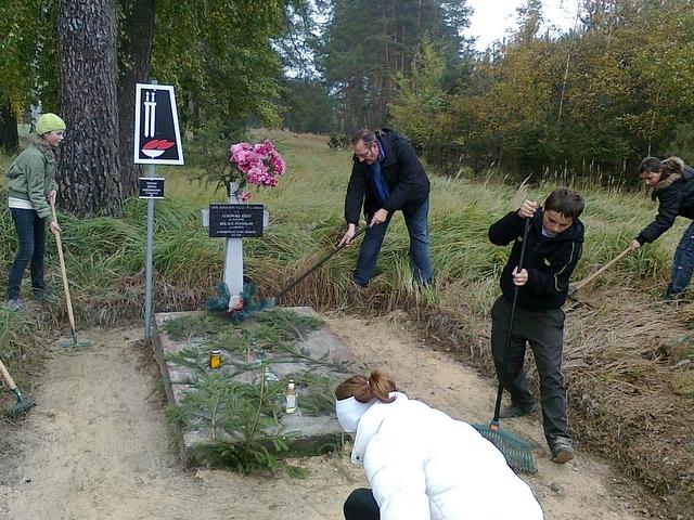 wie uporządkowali grób i zapalili znicze w Lasku Białężyńskim
