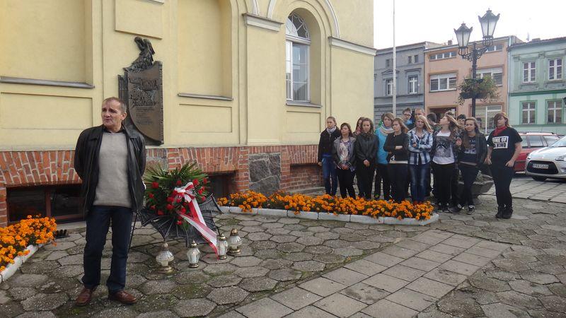 Uczniowie SP i Gimnazjum w Poniecu zapalili znicze pod tablicą na ścianie Ratusza