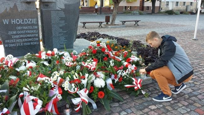 Adrian Buśkiewicz, uczeń I LO w Lesznie zapala znicz w miejscu pamięci w Gostyniu