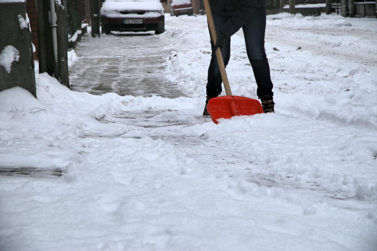 odśnieżanie szuflą, dozorca sprząta śnieg - Archiwum
